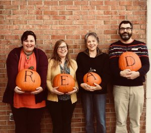 Staff and patron spelling out READ with pumpkins